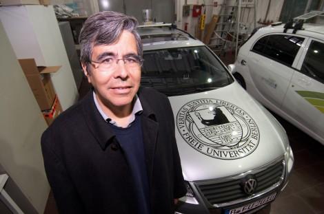 Professor Raúl Rojas vor seinem selbstfahrenden Auto mit dem Logo der FU. Foto: Cora-Mae Gregorschewski